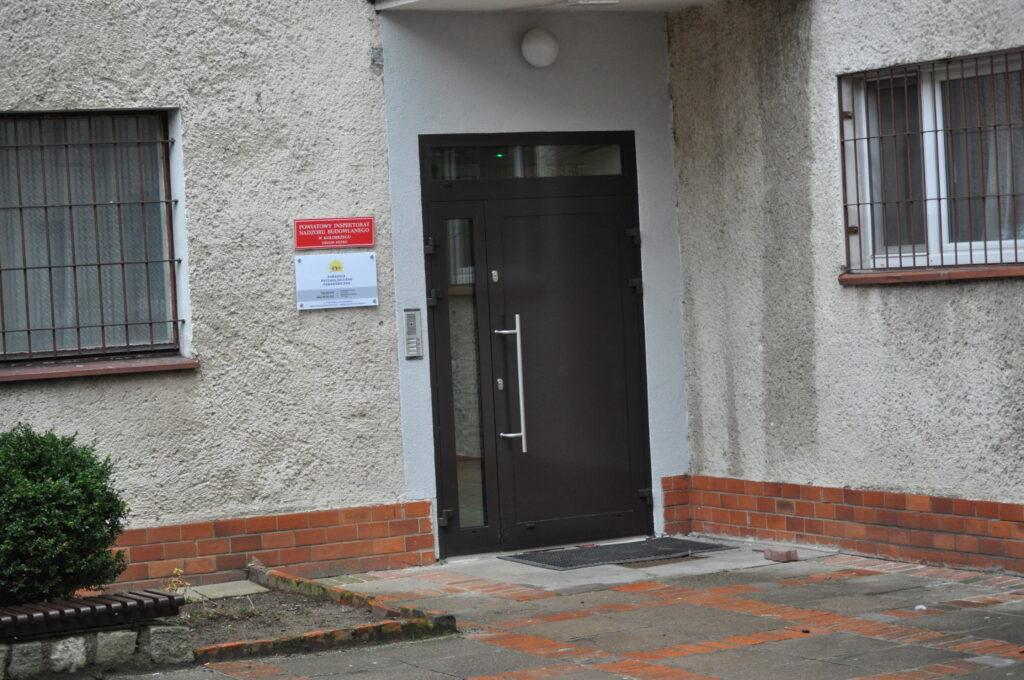 Zdjęcie przedstawia wejście od strony dziedzińca- przejście na dziedziniec drogą osiedlową usytuowaną przy budynku mieszkalnym przy Pl. 18 Marca (po lewej stronie budynku szkoły).