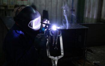 Zdjęcie przedstawiające ślusarza przy pracy.