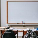 Zdjęcie poglądowe przedstawiające wnętrze szkolnej klasy: tablice i ławkę