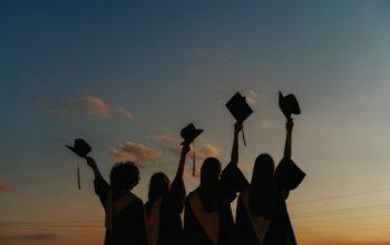 Zdjęcie poglądowe przedstawiające młodzież w togach podrzucającą birety