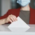 Zdjęcie przedsatwiające wyborcę wrzucającego kartkę z głosem do urny wyborczej